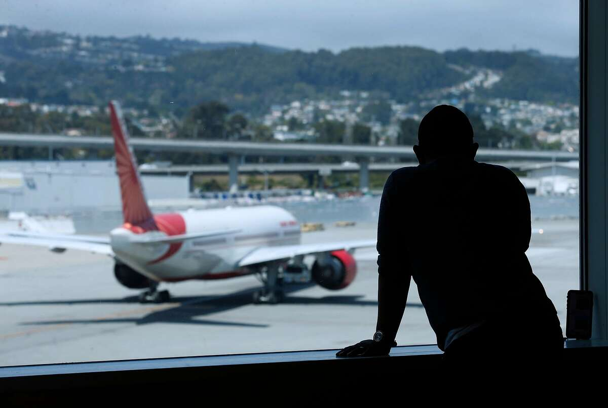 A traveler watches a passenger taxi away from the International Terminal before Rep. Mark DeSaulnier and retired airline Capt. Chesley �Sully� Sullenberger announce the Safe Landings Act legislation, inspired by the recent near-miss at SFO, during a news conference at SFO in San Francisco, Calif. on Thursday, Aug. 8, 2019.
