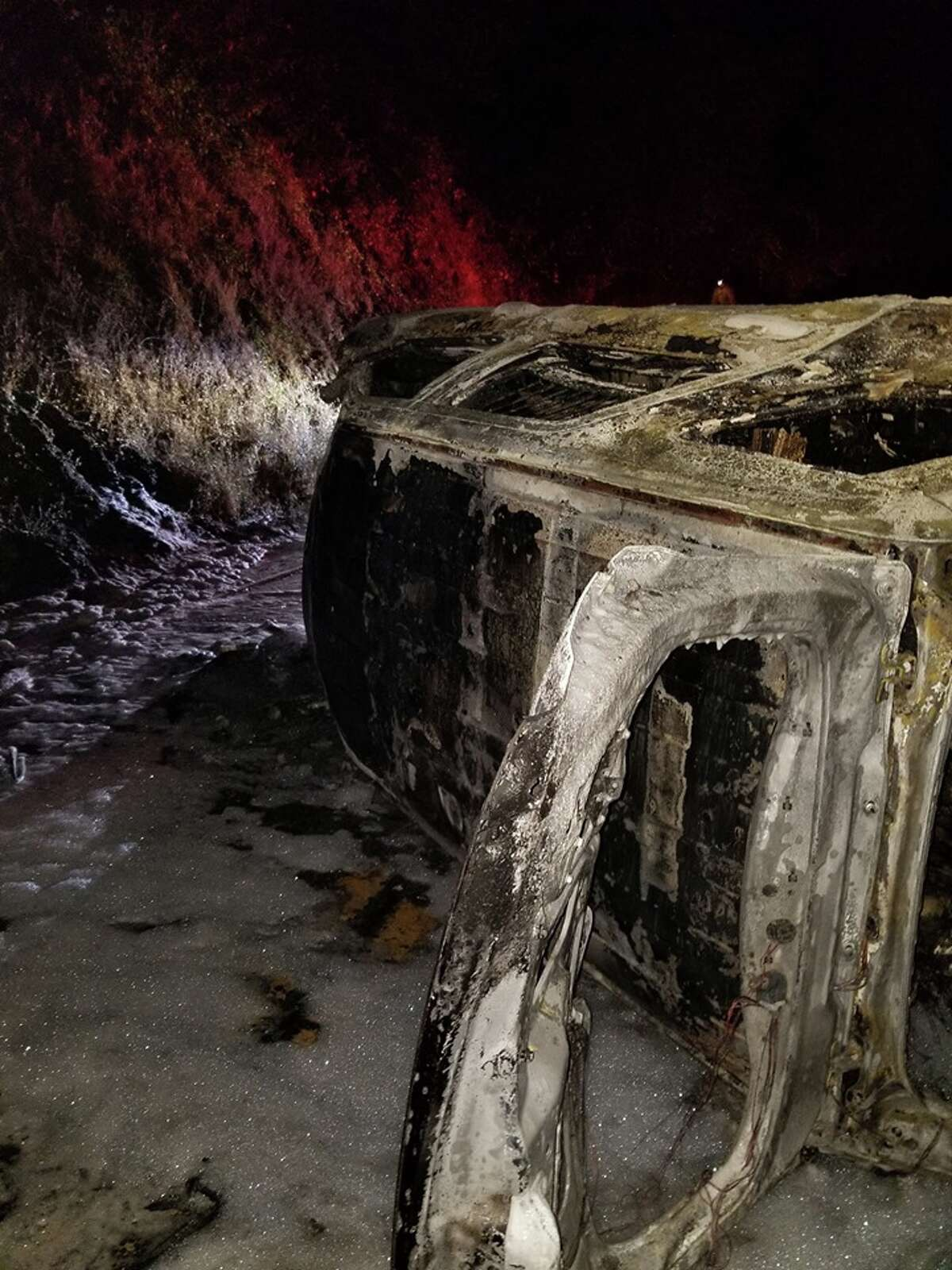 A Humboldt County sheriff's deputy's car is a charred shell after it caught fire Saturday on Highway 96 near Weitchpec. A bear that apparently fell off an embankment and landed on the vehicle is being blamed for the rollover crash.