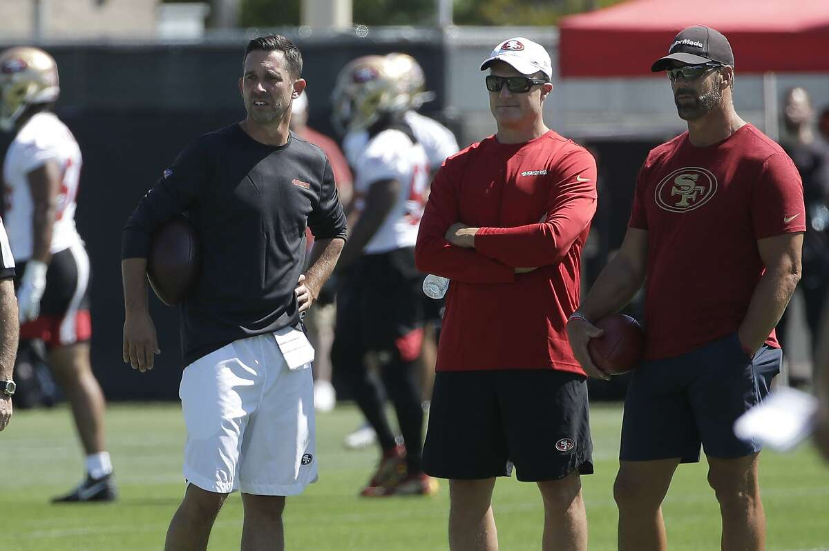 San Francisco 49ers head coach Kyle Shanahan, from left, watches as players practice with general manager John Lynch and broadcaster Tim Ryan at the team's NFL football training camp in Santa Clara, Calif., Saturday, July 27, 2019. (AP Photo/Jeff Chiu)