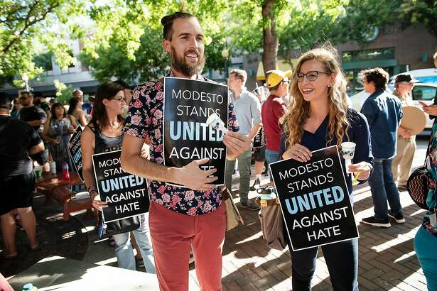 Shaun Gepley, and Katy Forney, right, attend a rally to show of opposition to a straight pride rally planned for Graceada Park. Dozens of people gathered before the Modesto City Council meeting at 10th Street Place in Modesto, Calif., Wednesday, Aug. 7, 2019.