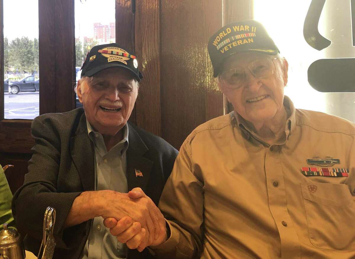 Bill Orlin (left), Holocaust survivor and Korean War veteran, and Bill Kongable, World War II veteran and Holocaust liberator, swap conversation and a handshake at a luncheon on Tuesday, Aug. 6, at Kenny & Ziggy's New York Delicatessen Restaurant on Post Oak. The Jewish deli is raising funds for the Holocaust Museum Houston during August with a special menu for National Deli Month.