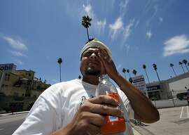 Wilfredo Aguilar wipes sweat from his forehead as he takes a break from painting a building under the hot sun on Hollywood Boulevard in Los Angeles, Thursday, June 19, 2008. Southern California roasted Thursday in a record-breaking, end-of-spring heat wave that sent temperatures soaring past 100 degrees in many areas, posing hazards for anyone who ventured outside. (AP Photo/Kevork Djansezian)