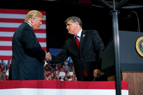 """President Donald Trump greets Fox commentator Sean Hannity onstage at a campaign rally on the eve of the 2018 midterm elections in Cape Girardeau, Mo. The event featured a local hero, Missouri-native Rush Limbaugh. The message was """"Be afraid."""" The president and his co-partisans have lately doubled down on it for the 2020 elections."""