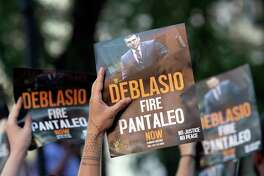 This Aug. 2, 2019 file photo shows demonstrators holding signs while calling on New York Mayor Bill de Blasio to fire police officer Daniel Pantaleo during a rally outside New York Police Department headquarters, in New York. Mayor Bill De Blasio's handling of the death of Eric Garner at the hands of Pantaleo and other officers in 2014 permanently poisoned his relationship with officers and also many of the activists who had helped elect him as a reformer. Both sides are now following around the country as he campaigns for the Democratic nomination for president.(AP Photo/Mary Altaffer, FILE )