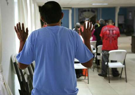 A man from Central America raises his hands in prayer during a prayer service at Senda De Vida Shelter in Reynosa, Tamaulipas. Central Americans have been flooding across the Texas-Mexico border.