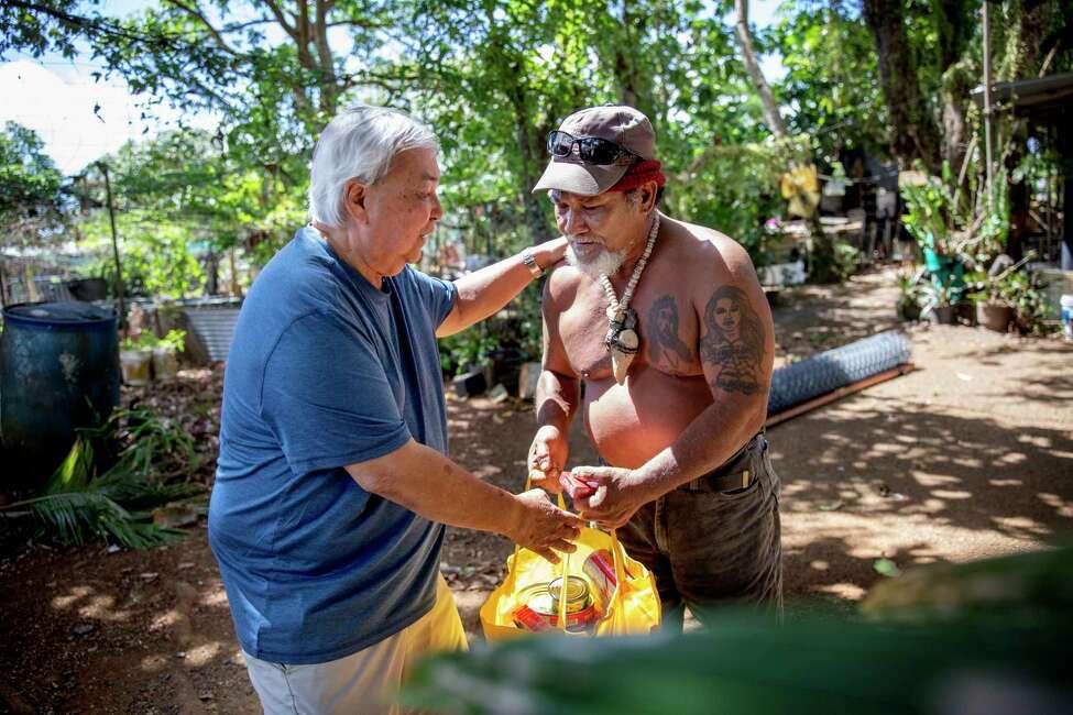 Leo Tudela, left, brings food for Everett Torregrosa as he visits his home in Hagatna, Guam, Thursday, May 9, 2019.