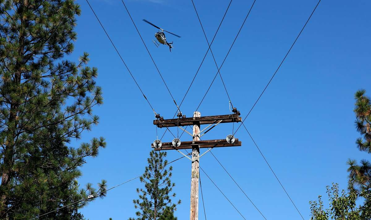 A PG&E helicopter flies 300 feet above inspecting power lines, as PG&E performs a public safety power shutoff drill around Foresthill, Ca. on Thurs. August 8, 2019, Helicopters and trucks, are used in a trial run for how it will inspect power lines before turning them on after a shut down.