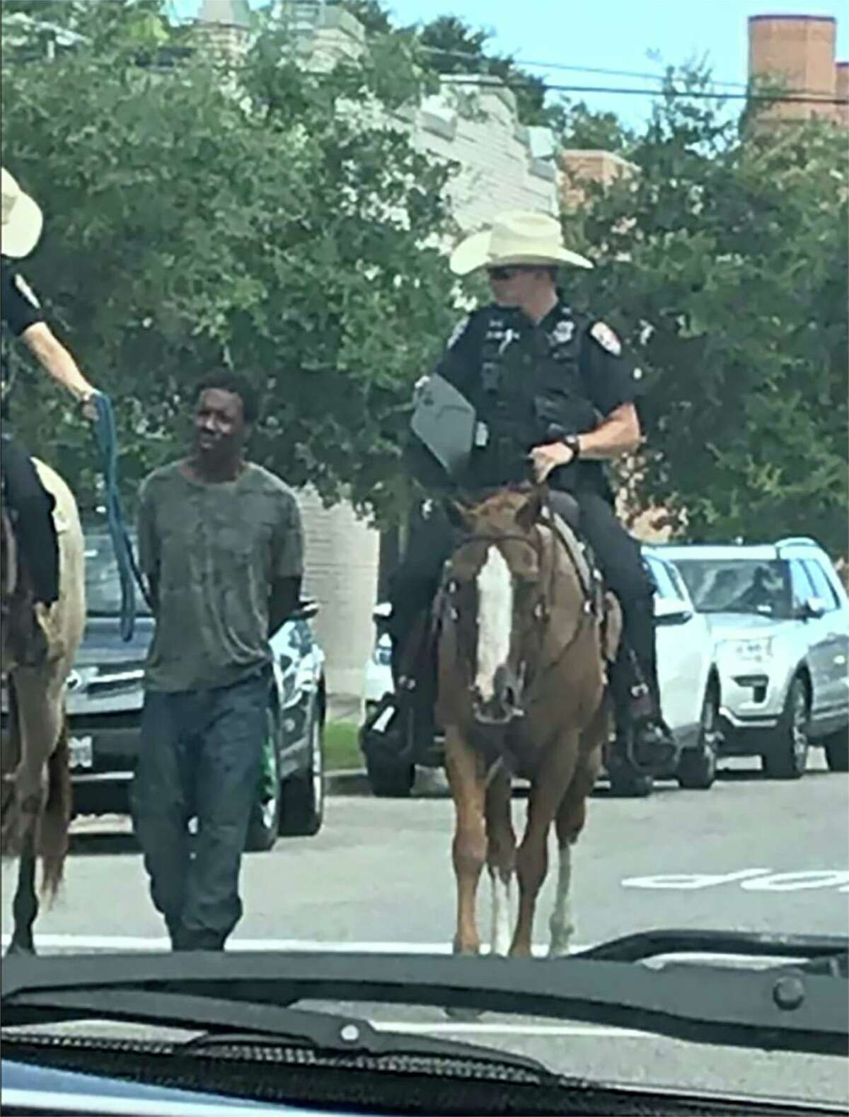 """Donald Neely, 43, is led by two Galveston police officers on horseback on Saturday. On Monday, a statement attributed to Chief Vernon L. Hale III said, """"Although this is a trained technique and best practice in some scenarios, I believe our officers showed poor judgment in this instance and could have waited for a transport unit at the location of the arrest."""""""