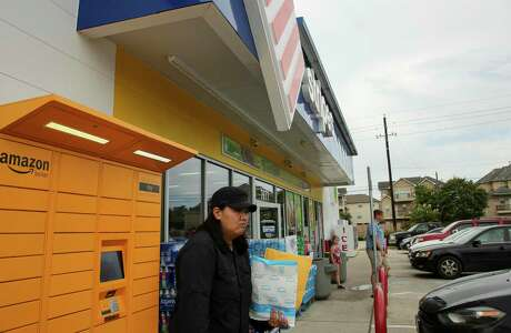 Victoria Pham picks up a package from an Amazon locker located at the Sunoco gas station on the 7600 block of Gessner Road Sunday, July 28, 2019, in Houston.