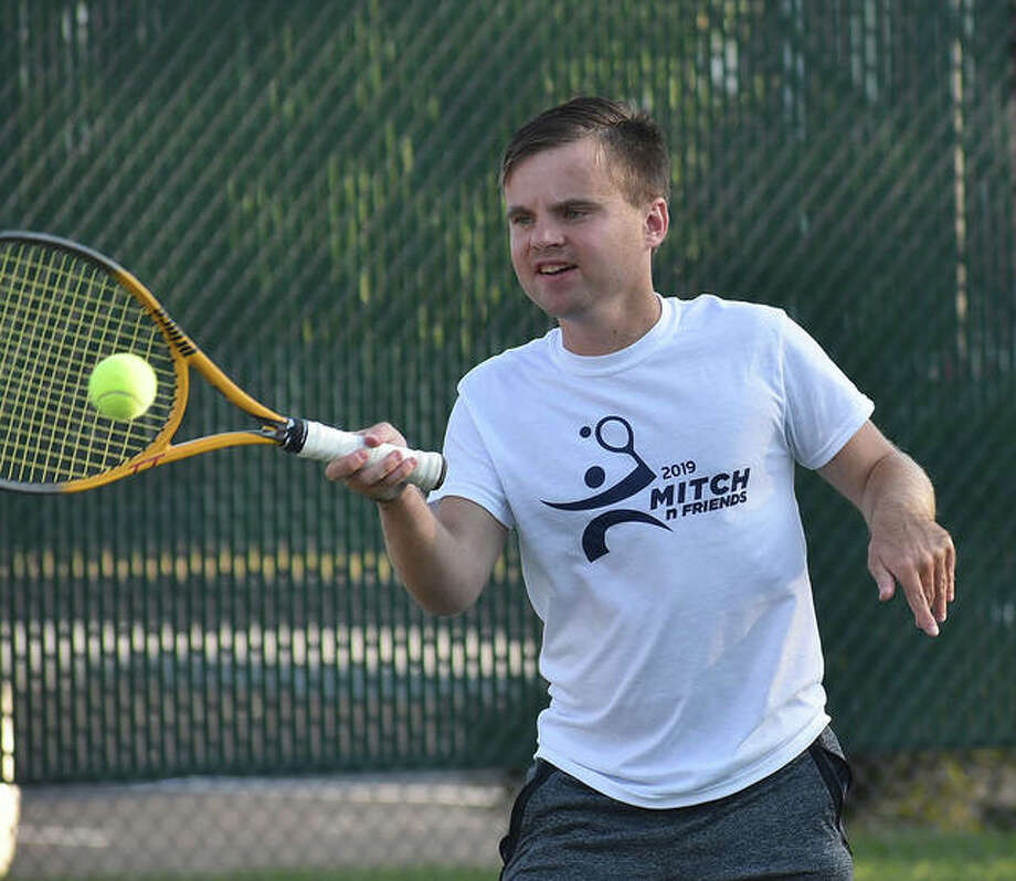 Mitchell McGinnis is all smiles as he hits the ball with Eric Sock during Mitch 'n' Friends on Thursday at the EHS Tennis Center. Photo: Matt Kamp|The Intelligencer
