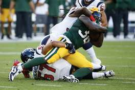 Houston Texans linebacker Brennan Scarlett (57) stops Green Bay Packers running back Tra Carson (32) during an NFL preseason football game against the Green Bay Packers at Lambeau Field in Thursday, Aug. 8, 2019, in Green Bay, Wis.