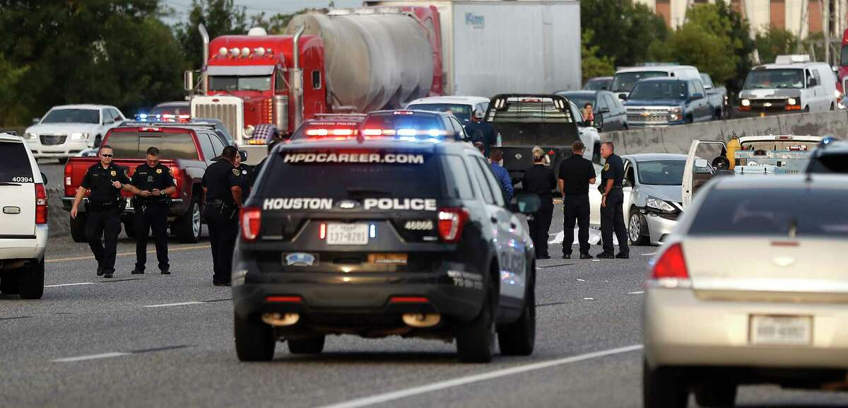 Houston Police investigate the scene where two people were shot and killed during rush hour on I-10 East near Mercury Drive, Thursday, August 8, 2019.