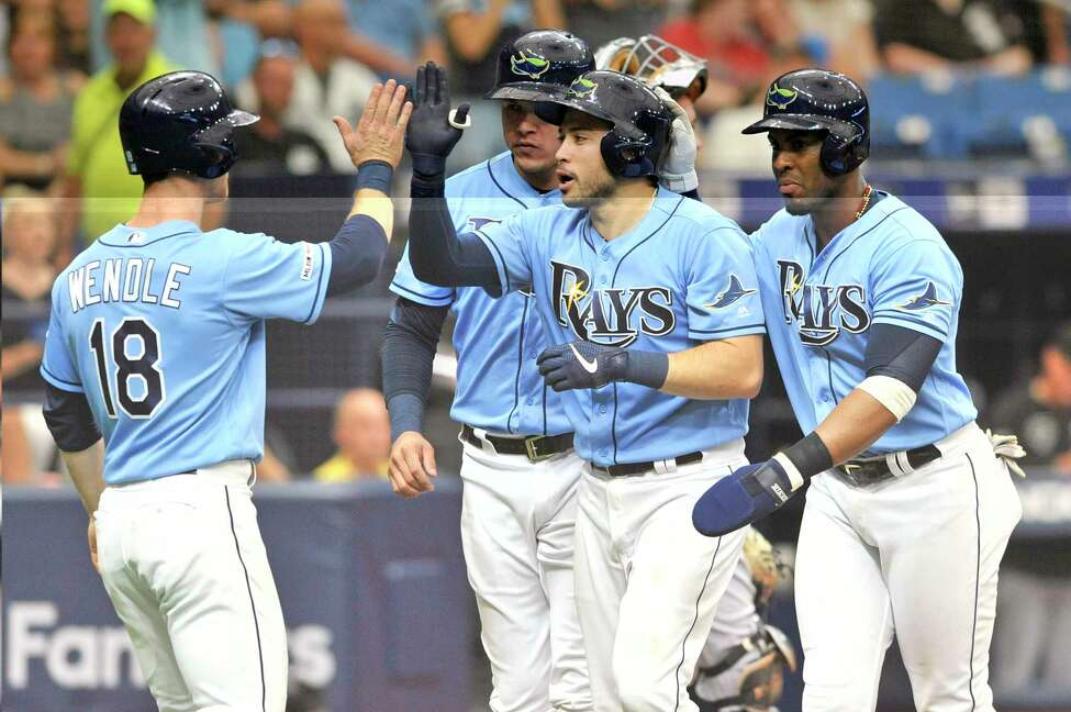FILE - In this July 21, 2019, file photo, from left to right, Tampa Bay Rays' Joey Wendle, Avisail Garcia, Travis d'Arnaud and Yandy Diaz celebrate d'Arnaud's grand slam off Chicago White Sox starter Dylan Cease during the second inning of a baseball game in St. Petersburg, Fla. Travis d'Arnaud is making the most of an opportunity to jumpstart his career with the Tampa Bay Rays, who are getting a lot more production from him than they anticipated when they acquired the 30-year-old catcher for a mere $100,000. (AP Photo/Steve Nesius, File)