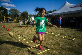Ruty Hsu of Saginaw, 8, runs through an obstacle course during a 100th anniversary picnic at the Greater Midland Community Center on Thursday, Aug. 8, 2019. (Katy Kildee/kkildee@mdn.net)