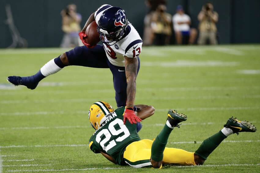Houston Texans wide receiver Tyron Johnson (14) fights to break away from Green Bay Packers cornerback Ka'dar Hollman (29) during a preseason NFL football game at Lambeau Field in Thursday, Aug. 8, 2019, in Green Bay, Wis.