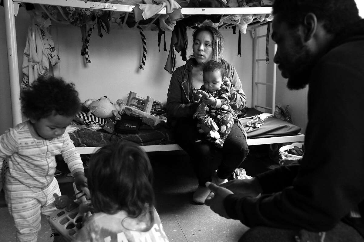 (8:42a.m.) Diana Cisnero, holds her daughter, Sandra, as Ellarose, left, Juston, and Derelle Foster surround her inside their room at Hamilton Families on Golden Gate Ave. Tuesday June 18, 2019.