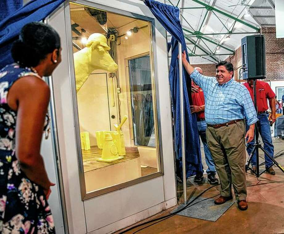 "Illinois Gov. JB Pritzker (center) and Illinois Lt. Gov. Juliana Stratton (left) unveil the 2019 Illinois State Fair Butter Cow during a ceremony Wednesday inside the Dairy Building on the Illinois State Fairgrounds in Springfield. The theme of this year's butter cow, made by artist Sarah Pratt using 800 pounds of recycled butter, is ""Building Our Future."" It contains nine hearts hidden within the sculpture that represent the essential nutrients found in dairy products. Photo: Justin L. Fowler 
