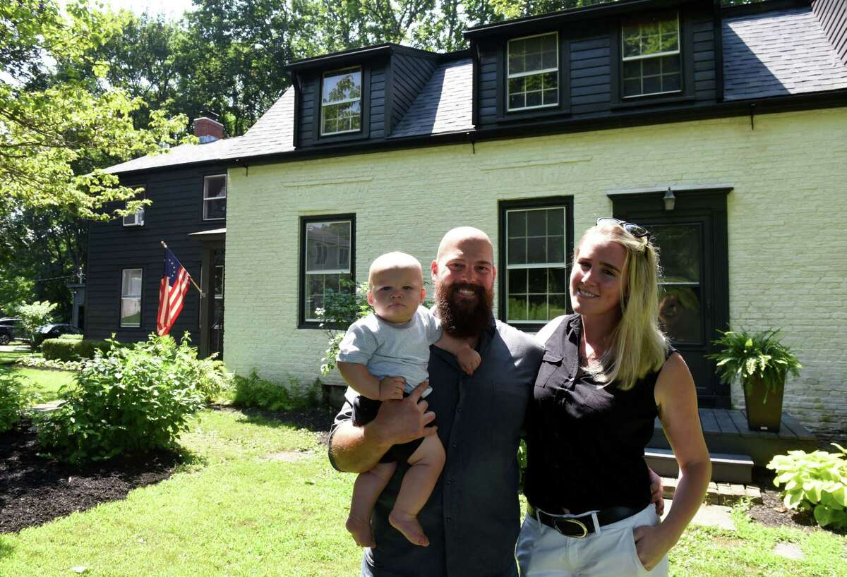 Travis and Elizabeth Martin stand outside their historic home with son, Hudson, on Tuesday, July 30, 2019, on Jordan Road in North Greenbush, N.Y. (Will Waldron/Times Union)