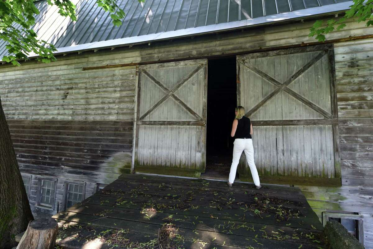 Elizabeth Martin opens the door to her historic barn on Tuesday, July 30, 2019, on Jordan Road in North Greenbush, N.Y. (Will Waldron/Times Union)