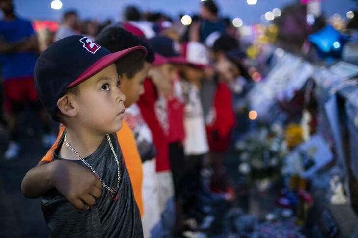 Aidan Gomez, 7, along with fellow members of two youth baseball teams gather at a makeshift memorial to honor victims of the Walmart shooting in El Paso.
