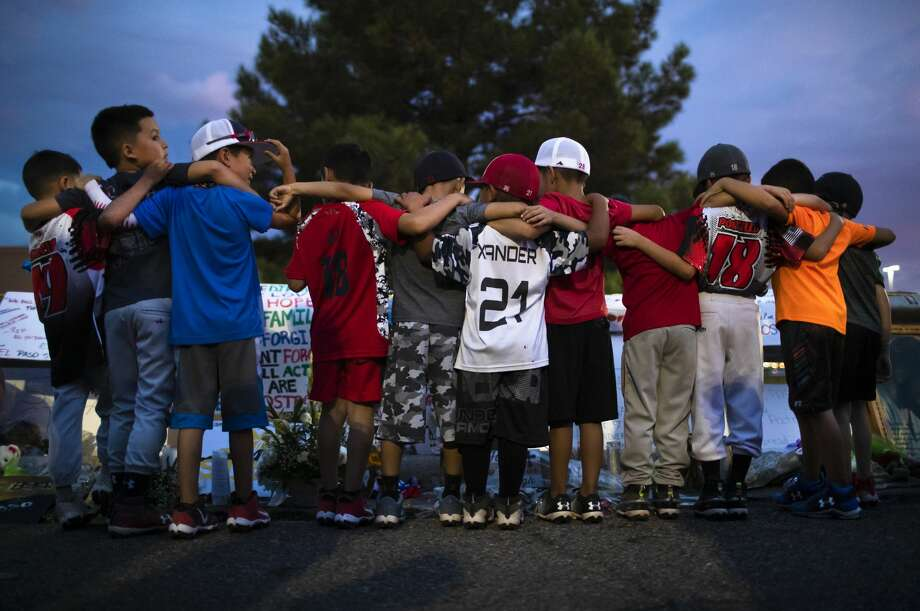 Xsquad and the Hit Squad baseball teams gather at a makeshift memorial to honor the victims of the Walmart shooting in El Paso. Photo: Marie D. De Jesús/Staff Photographer