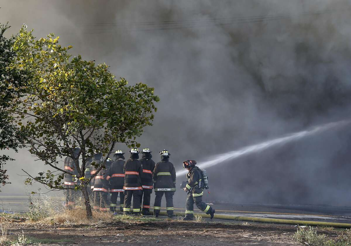 Firefighters battle a 3-alarm fire in a warehouse at 23rd Avenue and E. 11th Street in Oakland, Calif. on Friday, Aug. 9, 2019.
