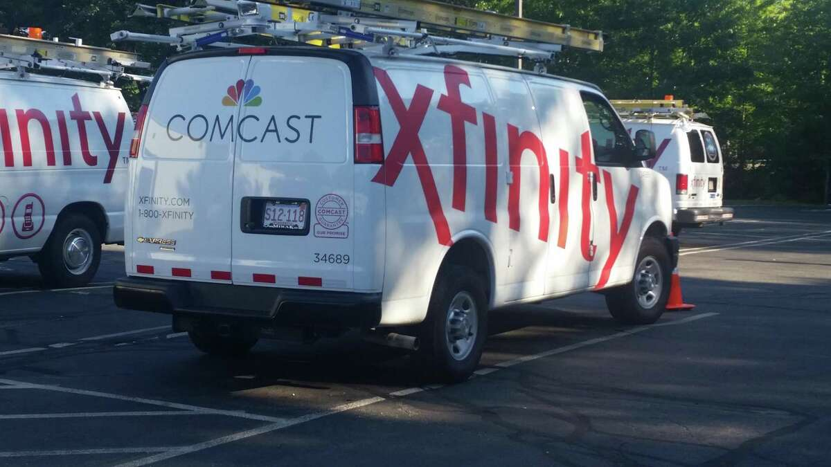 """FILE - In this Sept. 17, 2015, file photo, Comcast trucks are parked in a lot in the company's Westford, Mass. operations center. Cable companies have poured millions into new tools and hires to try to de-agonize the process of getting cable TV, internet or phone service. It's part of a years-long effort to try to assuage customers as the specter of """"cord-cutting"""" _ dumping cable for Netflix and the like _ haunts the industry. (AP Photo/Tali Arbel, File)"""