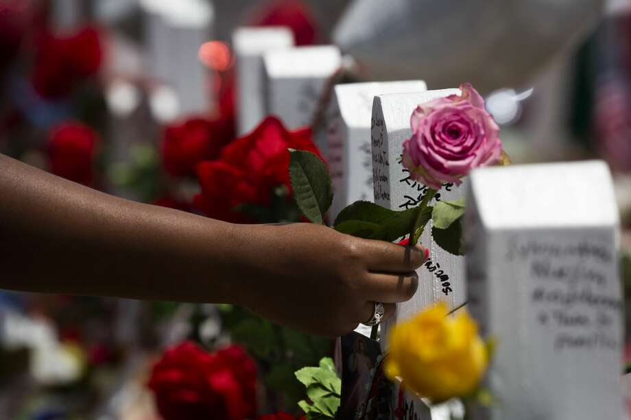 A woman places a rose on the crosses honoring the El Paso shooting victims at the makeshift memorial. Photo: Marie D. De Jesús/Staff Photographer
