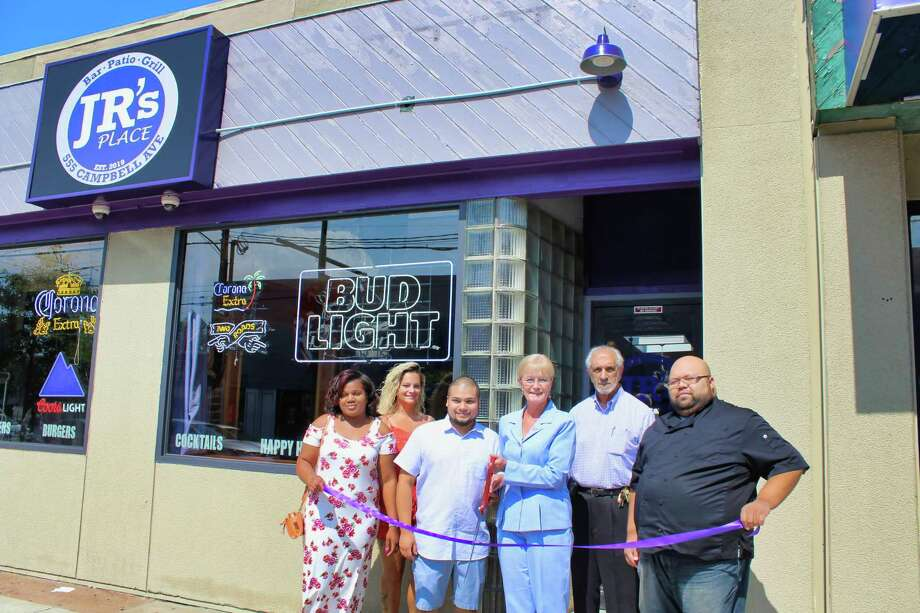 "JR's Place celebrates downtown opening: West Haven Mayor Nancy R. Rossi cuts the ceremonial ribbon Aug. 8 with JR's Place owner Russell Rivera, center, to celebrate the restaurant's grand opening at 555 Campbell Ave., formerly The Spot Bar and Grill. Also marking the event are, from left, Rivera's girlfriend, Tierra Pollock; JR's Place bartender Brenda Fronte; Rossi's executive assistant, Lou Esposito; and JR's Place chef Alberto Baez. Open seven days a week, the new downtown ""bar, patio and grill"" serves lunch and dinner and specializes in burgers, salads, bone-in and boneless wings, and hot and cold sandwiches. Along with cocktails, JR's Place offers domestic and imported beers, including India pale ales, and daily happy hour specials from 3-7 p.m. Photo: Michael P. Walsh - City Photo / Contributed"