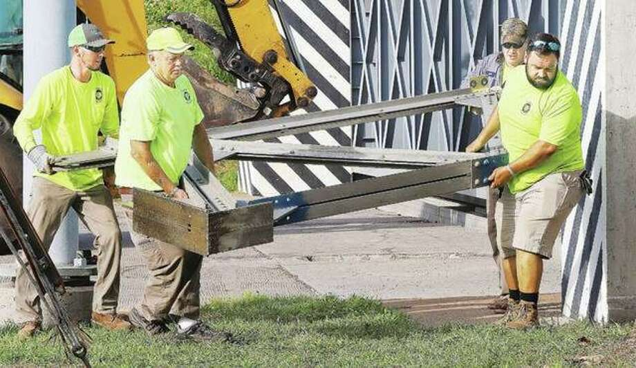East Alton Public Works Department employees carry one of the heavy braces from the flood gate back to its storage place.