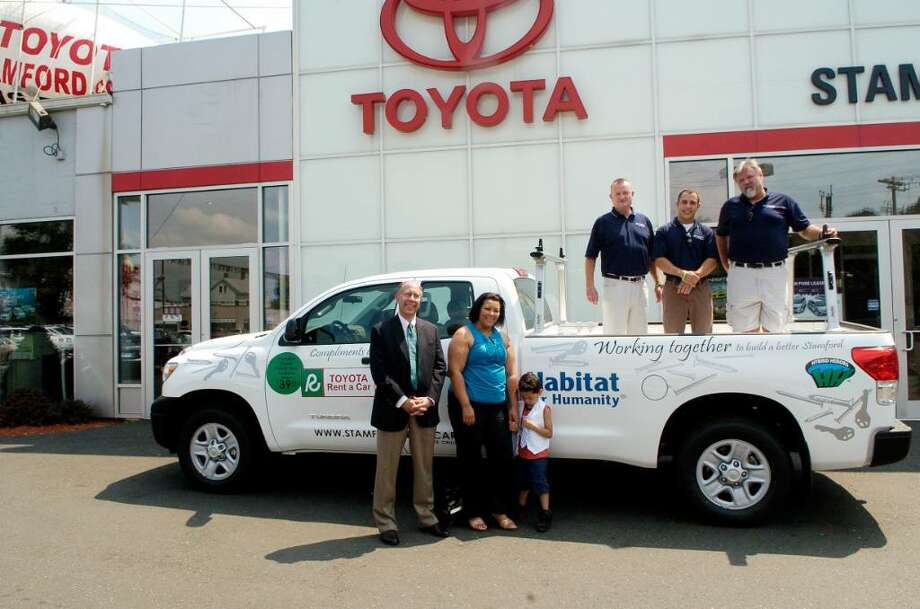Toyota of Stamford presents Habitat for Humanity of Coastal Fairfield County with a Tundra truck in Stamford, Conn. on Tuesday August 3, 2010, on the ground are Bruce Berzin, co-president of Habitat, Iveth Bowie, homeowner of Habitat home, her grandson Jaden Gonzalez in the truck John Linn, general manager Toyota, Raymond Campbell and Chuck McKale from Toyota. Photo: Dru Nadler / Stamford Advocate