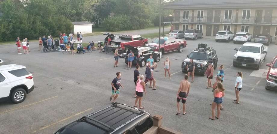 Fans and family members of Gladwin Post 171's baseball team have a party — including volleyball, cornhole, and a cookout — in the parking lot of the Unique Suites Hotel in Charleston, Ill., on Thursday evening. Photo: Photo Provided