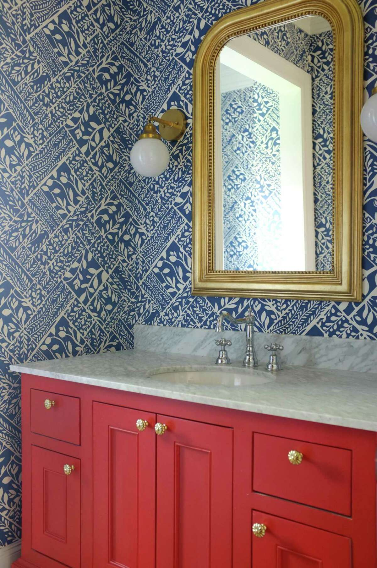 The cheerful powder bathroom has blue and white wallpaper and a coral-red vanity.