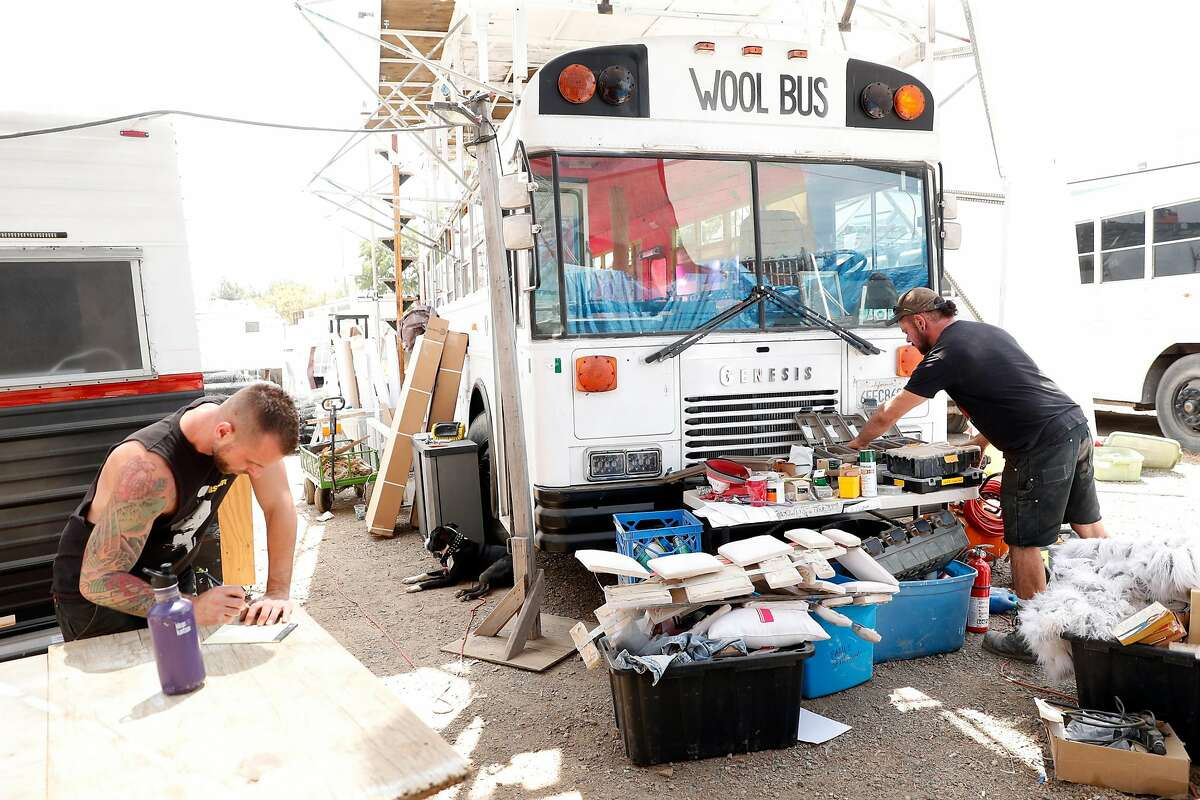 Artists Joey Matiz (left ) and Christian Williams ready a bus for Burning Man at NIMBY Collective warehouse in Oakland, Calif., on Monday, August 5, 2019.