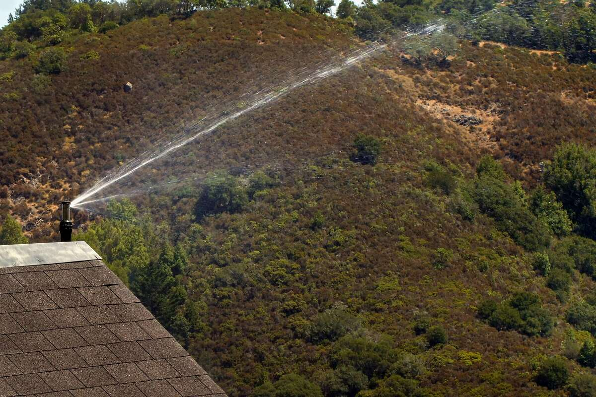 The exterior fire sprinkler system is tested by Frontline Wildfire Defense Systems is tested at the Cohen residence, Wednesday August 7, 2019, at their home in Mill Valley, Ca. Homeowners in fire-prone areas are taking extra precations for insurance and to protect their homes.