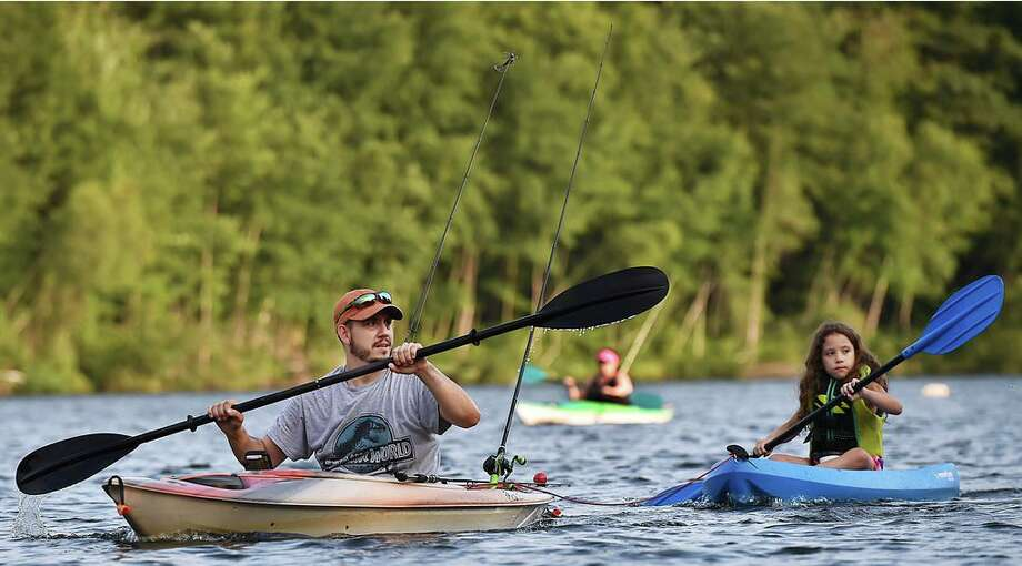 A man and his daughter paddle their kayaks, looking for a good spot to fish at Crystal Lake in Middletown. Photo: Hearst Connecticut Media File Photo / New Haven Register