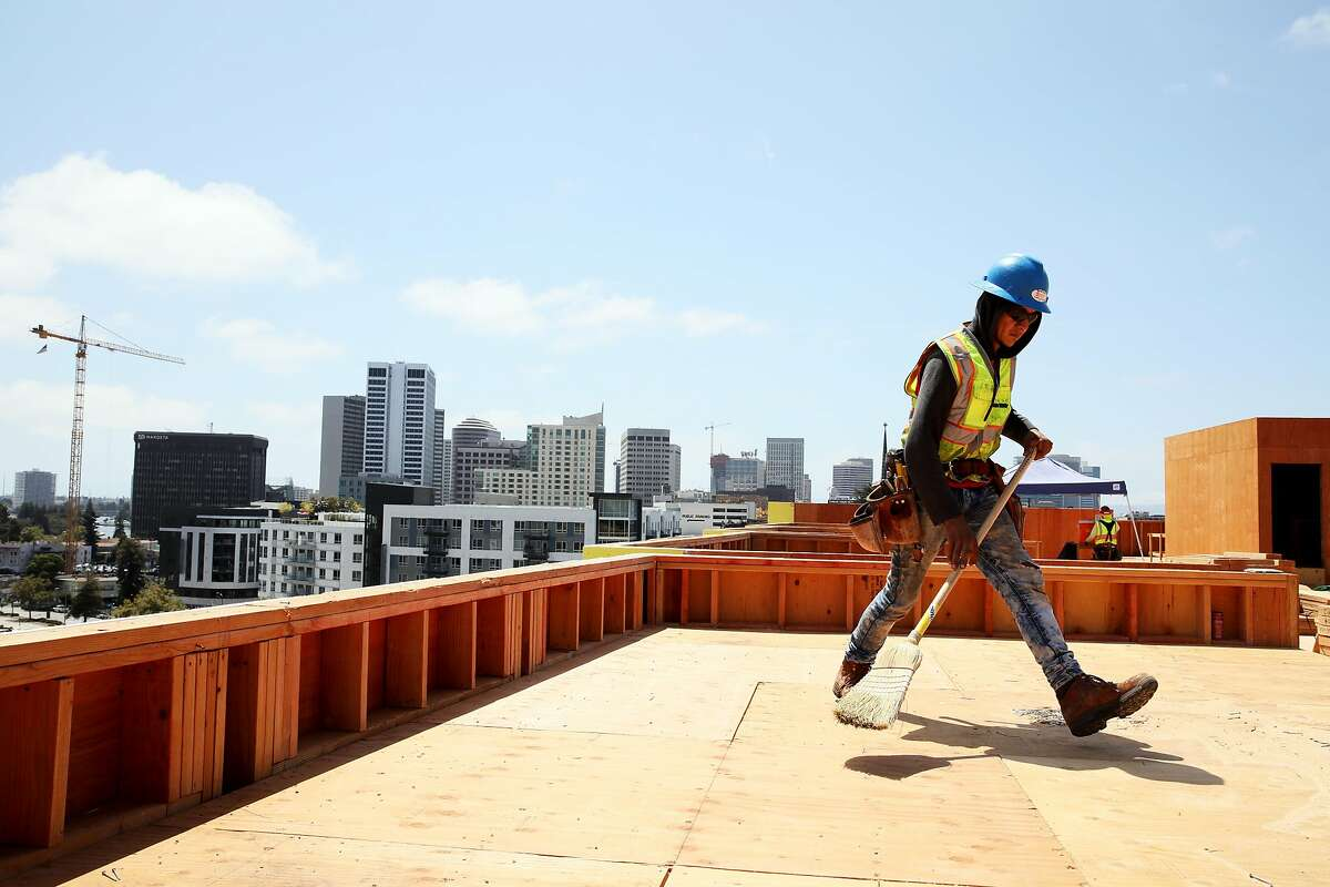 Oscar Ruiz sweeps the rooftop of 2855 Broadway Ave., the site of the Axis Broadway development that is under construction, in Oakland, Calif., on Thursday, August 8, 2019.