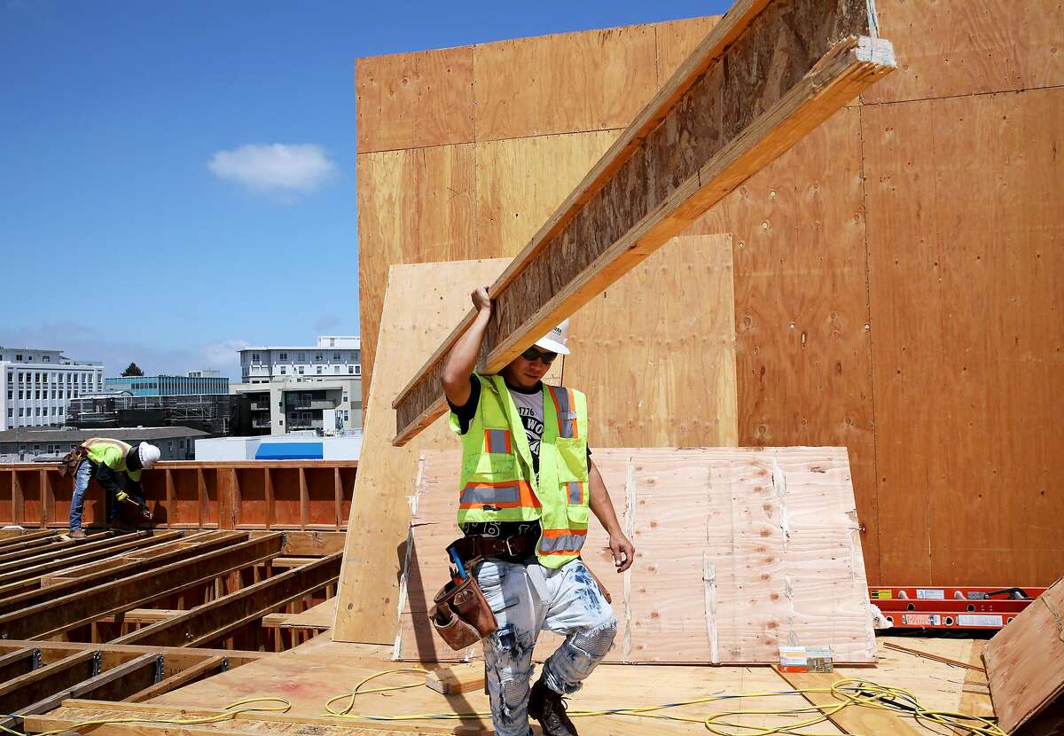 Jonathan Hernandez carries a beam on the rooftop of 2855 Broadway Ave., the site of the Axis Broadway development that is under construction, in Oakland, Calif., on Thursday, August 8, 2019.