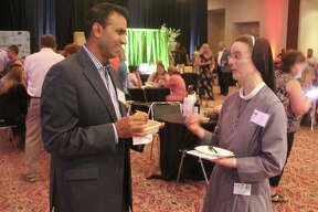 OSF Saint Anthonys President and CEO Ajay Pathak and Chief Operating Officer Sister M. Anselma talk at Farm-to-Table, a fundraiser for the Metro East chapter of the American Cancer Society held Thursday at Gateway Center in Collinsville. The event featured entertainment, food by local restaurants, and a number of other activities. The goal was $70,000 to be used for research and providing services for local cancer patients.