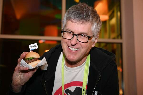 "Impossible Foods CEO Pat Brown holds up an Impossible Burger 2.0, the new and improved version of the company's plant-based vegan burger that tastes like real beef, at a press event during CES 2019 in Las Vegas, Nevada on January 7, 2019. - The updated version can be cooked on a grill and has a better flavor and lowered cholesterol, fat and calories than the original. ""Unlike the cow, we get better at making meat every single day,"" CEO of Impossible Foods CEO Pat Brown. (Photo by Robyn Beck / AFP) (Photo credit should read ROBYN BECK/AFP/Getty Images)"