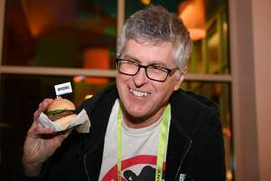"""Impossible Foods CEO Pat Brown holds up an Impossible Burger 2.0, the new and improved version of the company's plant-based vegan burger that tastes like real beef, at a press event during CES 2019 in Las Vegas, Nevada on January 7, 2019. - The updated version can be cooked on a grill and has a better flavor and lowered cholesterol, fat and calories than the original.  """"Unlike the cow, we get better at making meat every single day,"""" CEO of Impossible Foods CEO Pat Brown. (Photo by Robyn Beck / AFP)        (Photo credit should read ROBYN BECK/AFP/Getty Images)"""