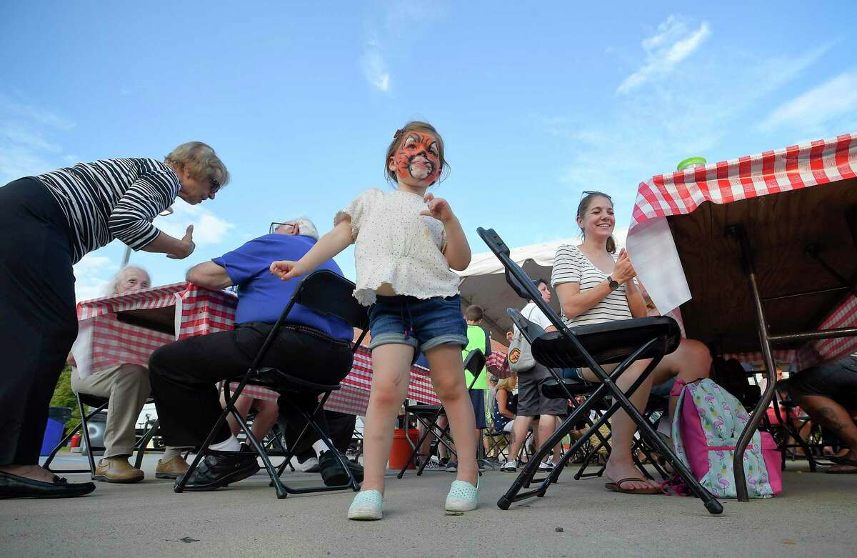 Norah Fehrs, 3, of Stamford dances to music during the annual St. Roch's Feast in Greenwich, Conn. on Aug. 8, 2019. The five day street festival, which includes the famous St. Roch Feast pizza fritta, a variety of foods, music, and fun carnival rides, proceeds raised benefit the church and its work in the community.