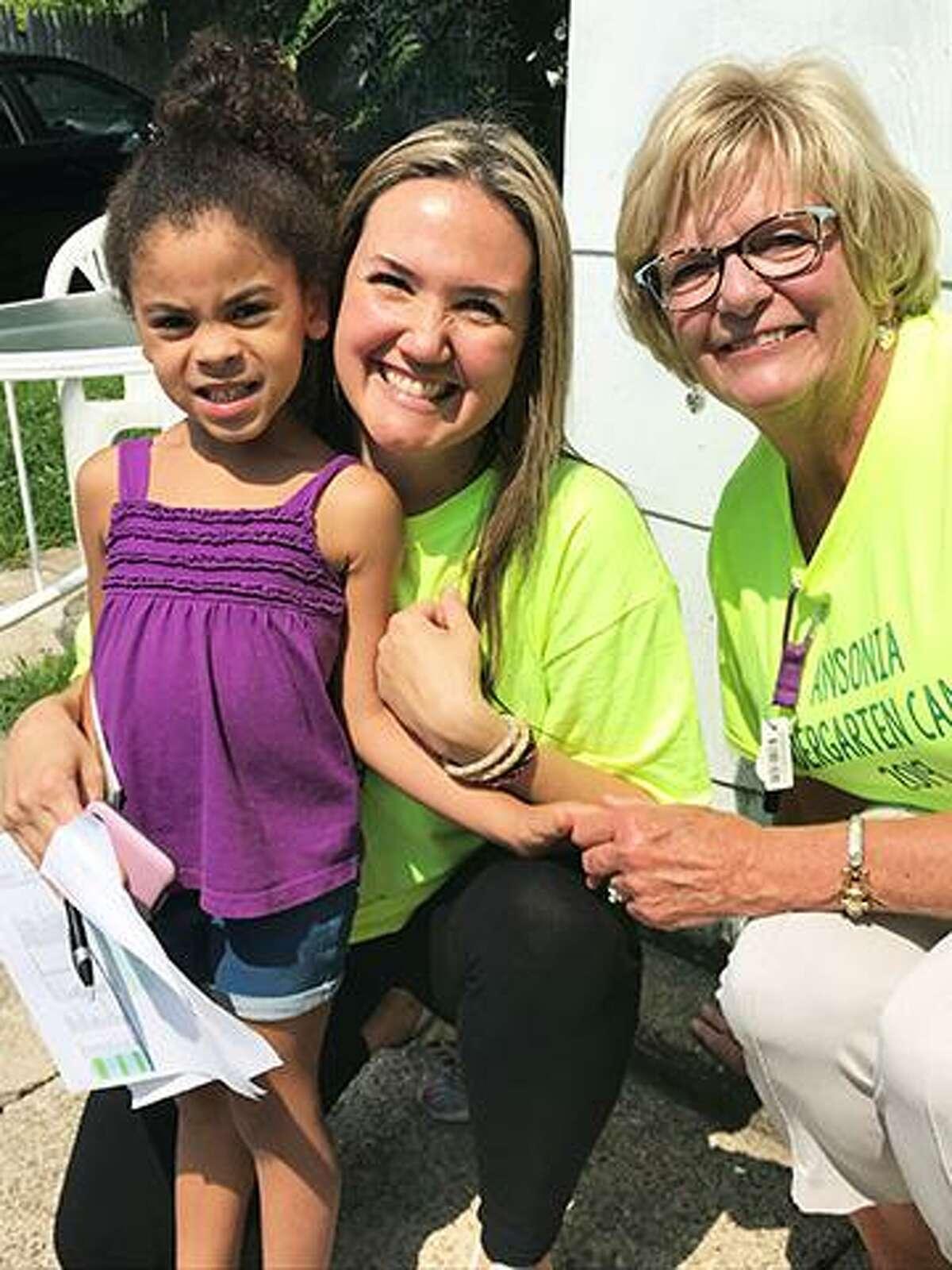 Mead School Principal Amy Cosciello, center, and teacher Patti Biga meet an incoming kindergarten student.