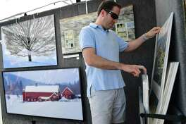 Jim Poucher of Fairfield looks at photoraphs by Ron Lake of Westport during the SoNo Arts Festival on Aug. 3 in Norwalk.