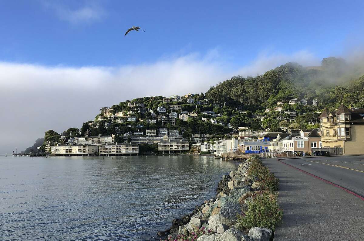 In this photo taken July 11, 2019, fog appears behind the hills of Sausalito, Calif.