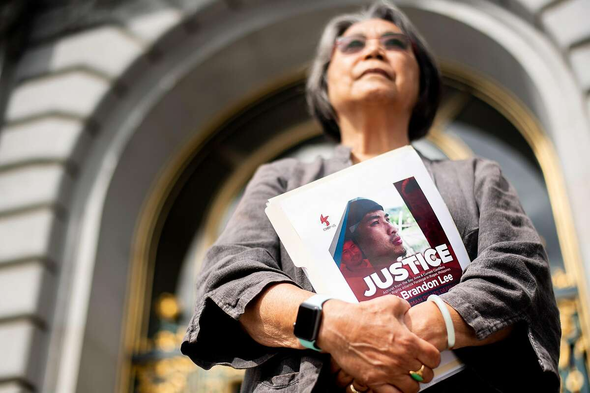 Pam Tau Lee holds a photo of Brandon Lee during a rally at San Francisco City Hall on Friday, Aug. 9, 2019, in San Francisco. Lee, an activist and community organizer, was shot outside his home in the Philippines, according to friends.