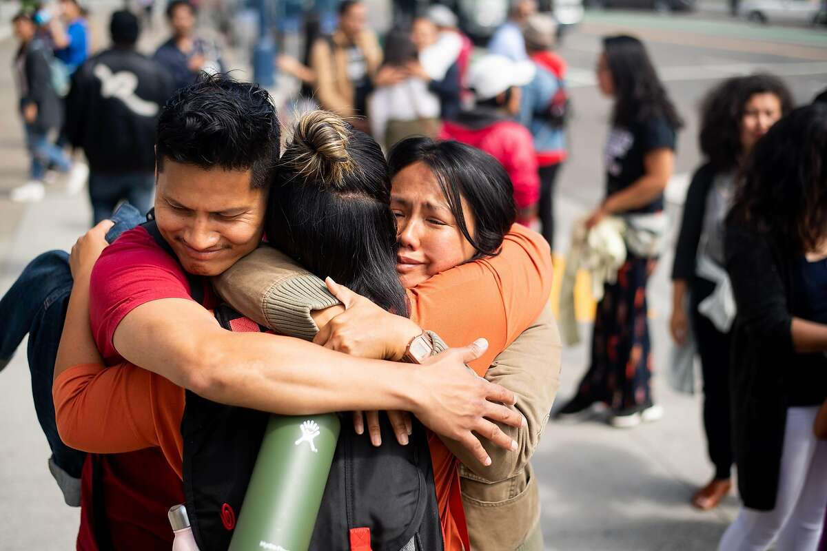 Tina Shauf-Bajar, right, and Mario De Mira, left, embrace a friend during a rally for Brandon Lee on Friday, Aug. 9, 2019, in San Francisco. Lee, an activist and community organizer, was shot outside his home in the Philippines, according to friends.