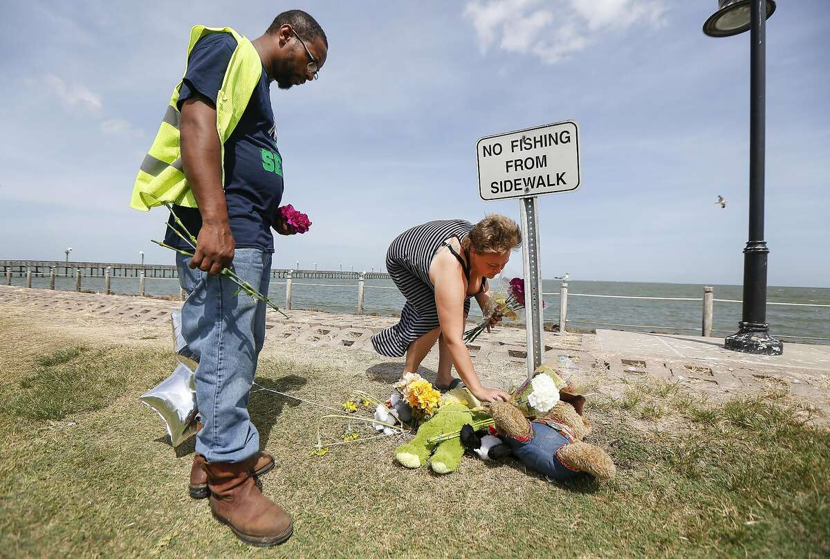 """Patrick January and his girlfriend Tasha Price lay flowers at one of two small memorials near the area where three siblings drowned Thursday night at Sylvan Beach Park in La Porte while playing in """"choppy"""" waters, officials said Friday, Aug. 9, 2019, in La Porte. The pair were at the beach and comforted the parents Thursday night. A fourth child - the eldest sibling in the family - was pulled from the water and taken by ambulance to the nearest hospital, said Harris County Sheriff Ed Gonzalez."""