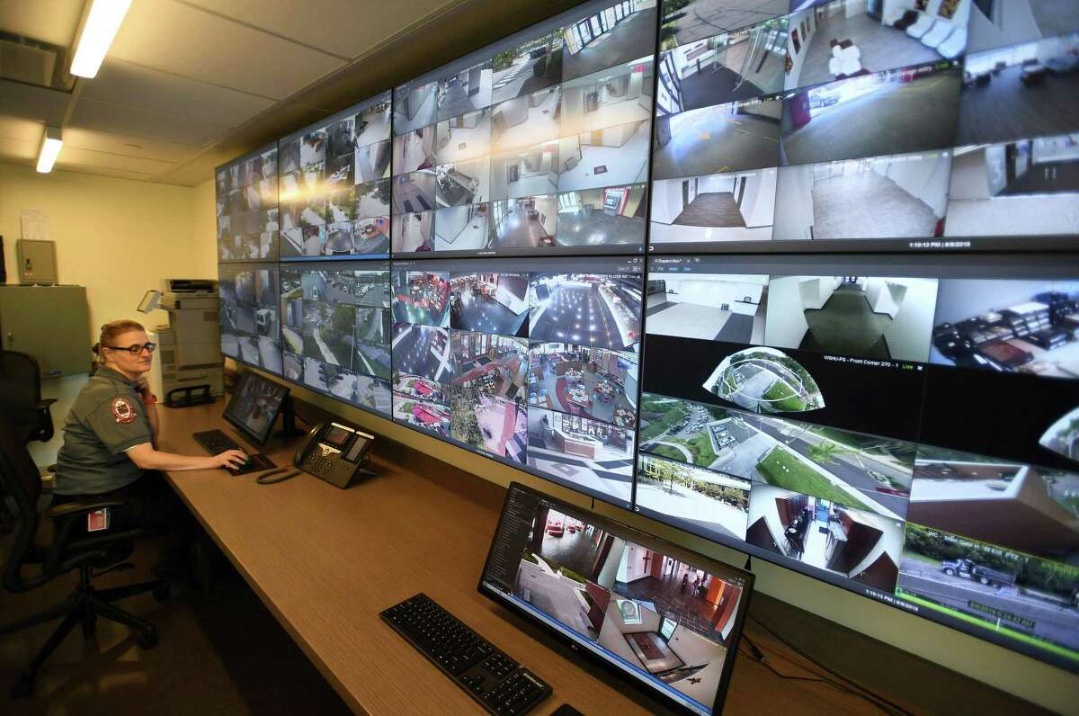 Dispatcher Kris Puzzo monitors a wall of displays from some of Sacred Heart University's one thousand video cameras at the school's Public Safety Headquarters on the campus in Fairfield, on Thursday.