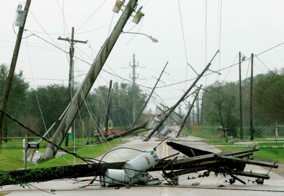 Electrical poles and lines are seen down, blown over by winds from Hurricane Ike, Saturday, Sept. 13, 2008, in Beaumont, Texas. (AP Photo/Tony Gutierrez) Photo: Tony Gutierrez, STF / AP / AP